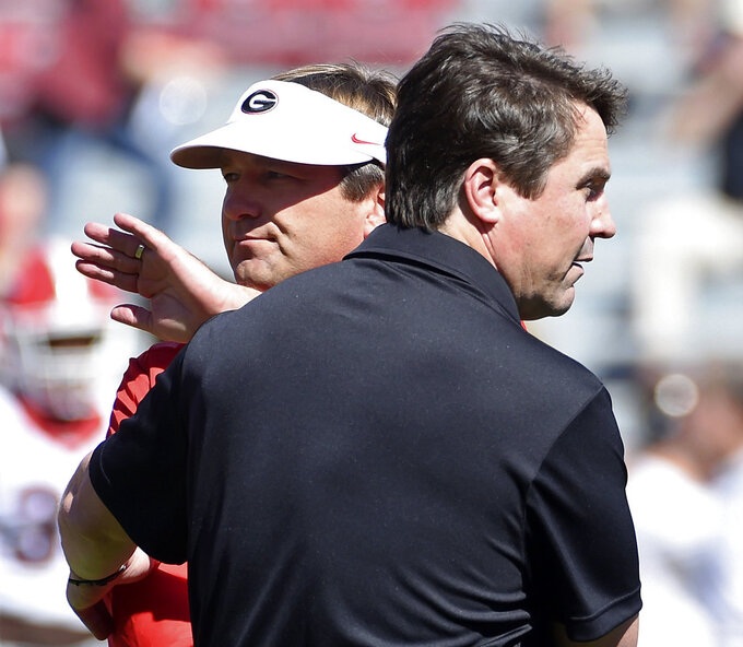 FILE - In this Oct. 9, 2016, file photo, Georgia head coach Kirby Smart, left, and South Carolina head coach Will Muschamp meet on the field before an NCAA college football game in Columbia, S.C. South Carolina has made constant improvement since bottoming out at the end of the Steve Spurrier era. But lose to Georgia on a high stakes SEC opener for both teams and the Gamecocks will likely spend another season in the national shadows. (AP Photo/Rainier Ehrhardt, File)