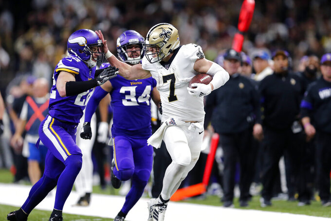 New Orleans Saints quarterback Taysom Hill (7) fends off Minnesota Vikings free safety Harrison Smith (22) on a long carry in the second half of an NFL wild-card playoff football game, Sunday, Jan. 5, 2020, in New Orleans. (AP Photo/Brett Duke)