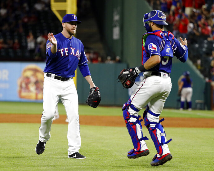 Texas Rangers relief pitcher Shawn Kelley, left, and catcher Isiah Kiner-Falefa, right, celebrate the team's 8-5 win in a baseball game against the Toronto Blue Jays in Arlington, Texas, Saturday, May 4, 2019. (AP Photo/Tony Gutierrez)