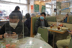 Customers have lunch with a transparent plastic panel setup on the table to isolate customers from spreading the coronavirus in Hong Kong, Wednesday, Feb. 12, 2020. China's ruling Communist Party needs to make a politically fraught decision: Admit a viral outbreak isn't under control and cancel this year's highest-profile official event. Or bring 3,000 legislators to Beijing next month and risk fueling public anger at the government's handling of the disease. (AP Photo/Kin Cheung)