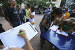 In this Feb. 19. 2019 photo, people fill forms to joint to the group of volunteers that will help to introduce humanitarian aid into Venezuela, during a meeting to recruit volunteers, at a square in Caracas, Venezuela. The volunteers anticipate running into roadblocks by soldiers who remain loyal to Maduro. They know that their chances of breaking through at first are slim, but they're undaunted. (AP Photo/Fernando Llano)