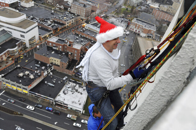 FILE - In this Dec. 6, 2013, file photo, New York Yankees general manager Brian Cashman rappels down One Landmark Square during a charity event in Stamford, Conn. While Cashman was descending the Landmark Building on Friday, Dec. 6, 2019, in preparation for a holiday celebration this weekend, the Yankees' general manager came across a message taped to a 10th-floor window from a fan: Please sign Gerrit Cole. Cashman confirmed he met with Cole in California on Tuesday and spoke with free-agent pitcher Stephen Strasburg the following day.(Dru Nadler/Hearst Connecticut Media via AP, File)