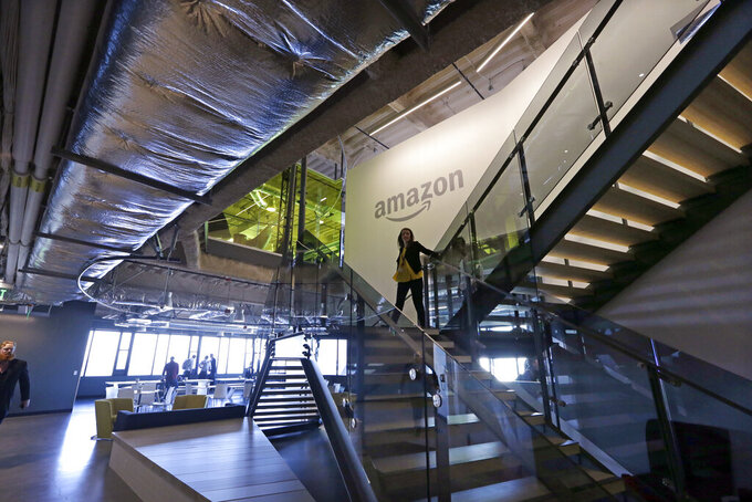 "FILE - In this Sept. 27, 2017, file photo, an Amazon worker walks down steps in a company office before an event announcing several new Amazon products by the company in Seattle. Amazon plans to have its employees return to the office by fall as the tech giant transitions away from the remote work it implemented for many workers due to the coronavirus pandemic. On Tuesday, March 30, 2021, the company told employees it is planning a ""return to an office-centric culture as our baseline."" (AP Photo/Elaine Thompson, File)"