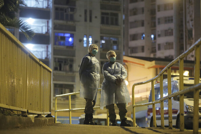 People wearing protective suits stand near the Cheung Hong Estate, a public housing estate, during evacuation of residents in Hong Kong, Tuesday, Feb. 11, 2020. The Centre for Health Protection of the Department of Health evacuated some residents from the public housing estate after a few cases of novel coronavirus infection to stop the potential risk of further spread of the virus. (AP Photo/Kin Cheung)