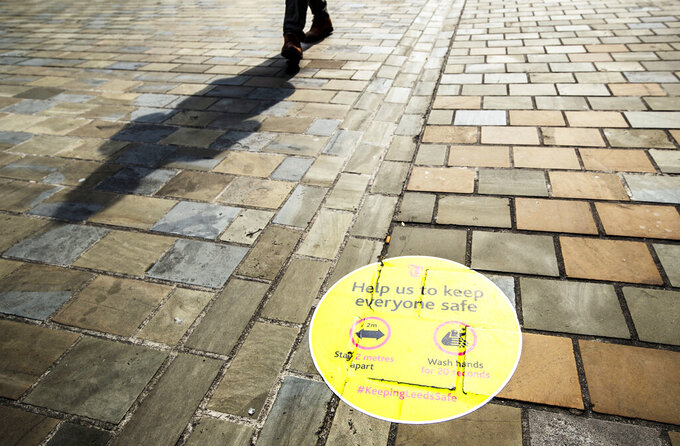 A person casts a shadow walking past a social distancing information sign painted on the pavement in Leeds city centre, England, Wednesday, Sept. 23, 2020. Local lockdowns are being imposed in several British cities where confirmed coronavirus infections have risen sharply. The council leader in the northern England city of Leeds says people will be barred from meeting members of other households indoors or in backyards. The measure affects more than 750,000 people.  (Danny Lawson/PA via AP)
