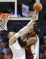 Florida State's Christ Koumadje, right, is fouled by Virginia's Jack Salt, left, during the first half of an NCAA college basketball game in the Atlantic Coast Conference tournament in Charlotte, N.C., Friday, March 15, 2019. (AP Photo/Chuck Burton)