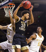 Wake Forest's Olivier Sarr (30) grabs a rebound over Notre Dame's John Mooney (33) and Juwan Durham (11) during the second half of an NCAA college basketball game Wednesday, Jan. 29, 2020, in South Bend, Ind. Notre Dame won 90-80. (AP Photo/Robert Franklin)