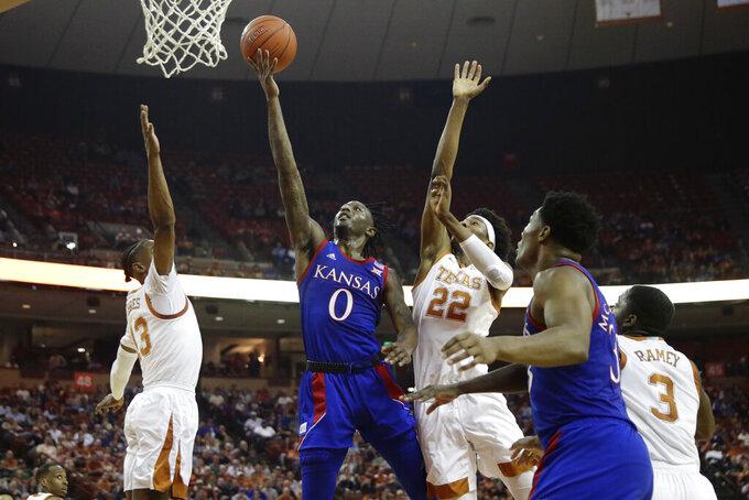 Kansas guard Marcus Garrett (0) shoots past Texas forward Kai Jones (22) during the first half of an NCAA college basketball game, Saturday, Jan. 18, 2020, in Austin, Texas. (AP Photo/Eric Gay)