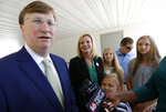 Republican Lt. Gov. Tate Reeves, a gubernatorial candidate, left, responds to a reporter's question after voting in the party primary at a Flowood, Miss., precinct, with his family, Tuesday, Aug. 6, 2019. (AP Photo/Rogelio V. Solis)