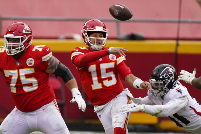 Kansas City Chiefs quarterback Patrick Mahomes throws a pass while being chased down by Atlanta Falcons Jacob Tuioti-Mariner during the second half of an NFL football game, Sunday, Dec. 27, 2020, in Kansas City. (AP Photo/Charlie Riedel)
