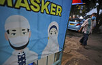 A man walks past a banner with a message encouraging people to always wear masks to help curb the spread of coronavirus outbreak, in Jakarta, Indonesia, Thursday, Dec. 3, 2020. (AP Photo/Dita Alangkara)