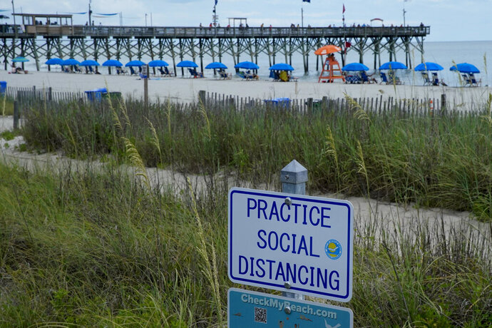 Beach umbrellas are separated in back of a sign urging social distancing on the sand Thursday, July 9, 2020, in Myrtle Beach, S.C. (AP Photo/Chris Carlson)