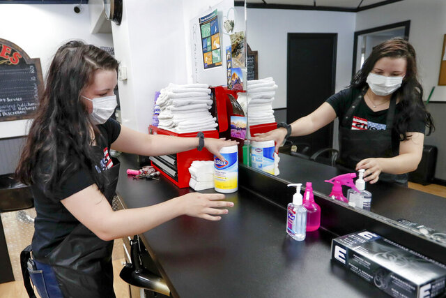 Stylist Kayla Addink arranges items in her workspace Thursday, June 4, 2020, as she prepares for her first day back on the job at the West View Barber Shop when most of southwest Pennsylvania loosens COVID-19 restrictions on Friday in West View, Pa. (AP Photo/Keith Srakocic)