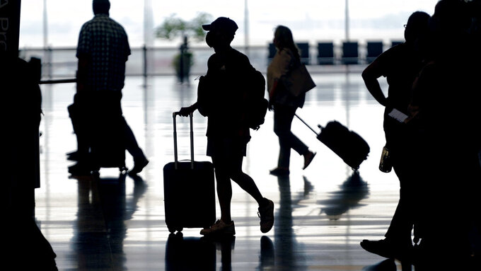 FILE - In this Tuesday, Aug. 17, 2021, file photo, travelers move through Salt Lake City International Airport in Salt Lake City. A COVID-19 resurgence this summer has caused consumers to turn cautious, while investors trim their investments in a travel sector still struggling to recover. (AP Photo/Rick Bowmer, File)