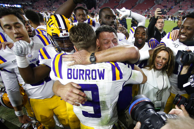 LSU head coach Ed Orgeron embraces quarterback Joe Burrow (9) after defeating Alabama 46-41 in an NCAA college football game, Saturday, Nov. 9, 2019, in Tuscaloosa, Ala. (AP Photo/John Bazemore)