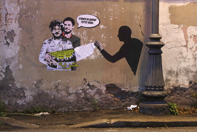 FILE - In this Feb. 19, 2020 file photo, a mural depicting detained Egyptian human rights advocate and student at the University of Bologna in Italy Patrick George Zaki, being hugged from behind by Italian researcher Giulio Regeni, who was murdered in Cairo in 2016, is displayed on a wall near a park, in Rome. An Egyptian court extended the detention of Zaki, an activist and researcher who previously worked for the Egyptian Initiative for Personal Rights, or EIPR, one of the country's most prominent rights groups, the group said on Monday. Writing in Italian at top reads: