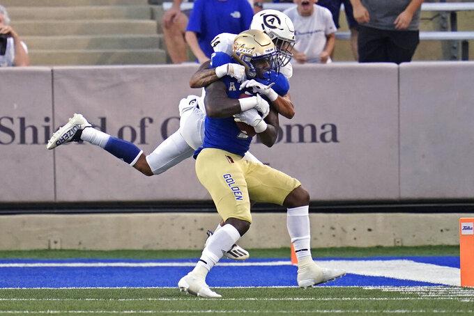 UC Davis defensive back Chris Venable (14) stops Tulsa wide receiver Sam Crawford Jr. during the first half of an NCAA college football game Thursday, Sept. 2, 2021, in Tulsa, Okla. (AP Photo/Sue Ogrocki)