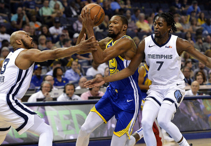Golden State Warriors forward Kevin Durant (35) drives between Memphis Grizzlies guard Jevon Carter (3) and forward Justin Holiday (7) during the first half of an NBA basketball game Wednesday, April 10, 2019, in Memphis, Tenn. (AP Photo/Brandon Dill)