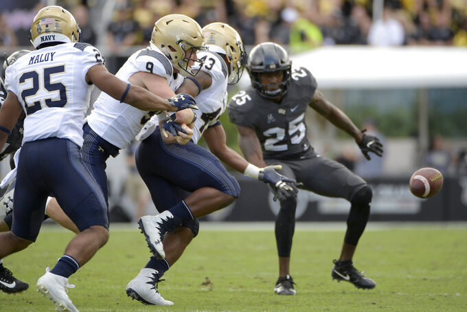 Navy quarterback Zach Abey (9) fumbles the ball in front of Central Florida defensive back Kyle Gibson (25) during the first half of an NCAA college football game Saturday, Nov. 10, 2018, in Orlando, Fla. (AP Photo/Phelan M. Ebenhack)