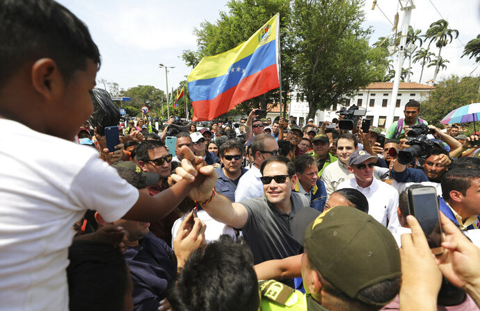 U.S. Senator Marco Rubio, R-Fla., greets Venezuelan migrants near the Simon Bolivar International Bridge, which connects Colombia with Venezuela, where one holds up Venezuelan flag in La Parada, near Cucuta, Colombia, Sunday, Feb. 17, 2019. As part of U.S. humanitarian aid to Venezuela, Rubio is visiting the area where the medical supplies, medicine and food aid is stored before it it expected to be taken across the border on Feb. 23. (AP Photo/Fernando Vergara)