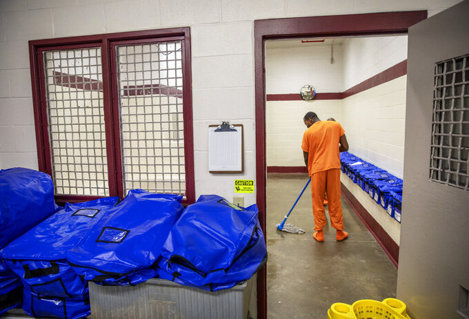 FILE - In this Nov. 15, 2019 file photo, a detainee mops the floor at the intake station at the Stewart Detention Center in Lumpkin, Ga. Federal authorities said a 57-year-old Mexican man who was being held in federal immigration detention at the center in southwest Georgia died on Saturday, Jan. 30, 2021, from complications of COVID-19. (AP Photo/David Goldman, File)