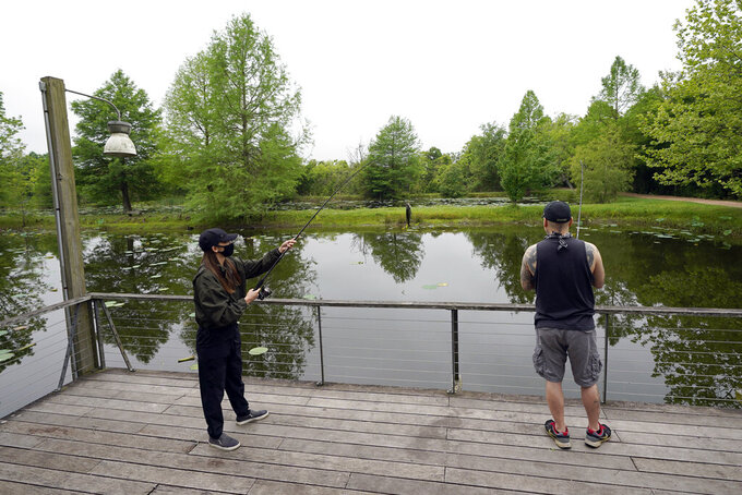 Susan Shin, left, catches a fish while fishing with her husband Chris, Monday, April 20, 2020, at Sheldon Lake State Park and Environmental Learning Center in Houston. Texas Gov. Greg Abbott has ordered state parks to reopen Monday after being closed due to the COVID-19 outbreak. (AP Photo/David J. Phillip)
