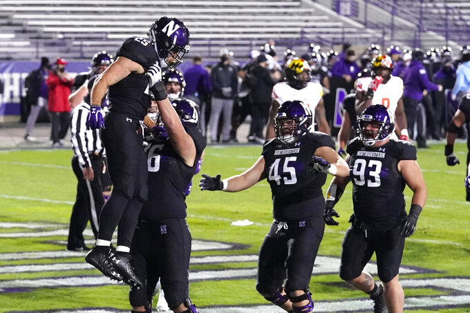 Northwestern running back Isaiah Bowser, left, celebrates with offensive line Ethan Wiederkehr, second from left, and teammates after scoring a touchdown during the first half of an NCAA college football game against Maryland in Evanston, Ill., Saturday, Oct. 24, 2020. (AP Photo/Nam Y. Huh)