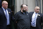 Marc Lamparello, 37, center, is escorted out of a police precinct in New York, Thursday, April 18, 2019.  Police say Lamparello was arrested after entering St. Patrick's Cathedral Wednesday night in New York with two cans of gasoline, lighter fluid and butane lighters. Lamparello is facing charges including attempted arson and reckless endangerment. (AP Photo/Seth Wenig)