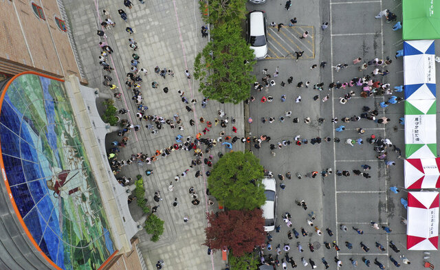 People wait in line for the new coronavirus tests at a church in Gwangju, South Korea, Friday, July 3, 2020. South Korea has reported 63 newly confirmed cases of COVID-19 as health authorities scramble to mobilize public health tools to the southwestern city of Gwangju, where more than 50 people were found sickened over the past week. (Chung Hoi-sung/Yonhap via AP)