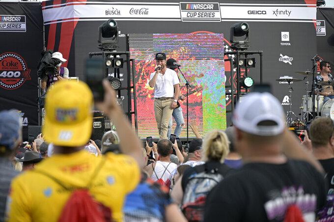 Entertainer Chris Lane, center, performs before a NASCAR Cup Series auto race at Daytona International Speedway, Saturday, Aug. 28, 2021, in Daytona Beach, Fla. (AP Photo/Phelan M. Ebenhack)