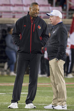 Louisville interim coach Lorenzo Ward, left, and Kentucky coach Mark Stoops meet on the field before an NCAA college football game in Louisville, Ky., Saturday, Nov. 24, 2018. (AP Photo/Bryan Woolston)