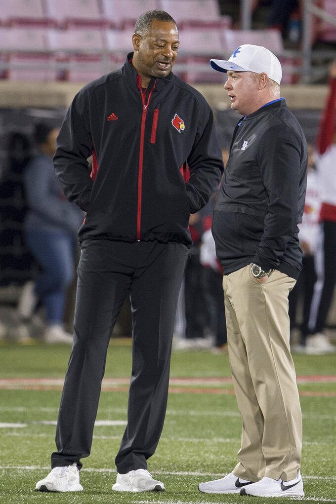 Louisville interim coach Lorenzo Ward, left, and Kentucky coach Mark Stoops meet on the field before an NCAA college football game in Louisville, Ky., Saturday, Nov. 24, 2018. (AP Photo/Bryan Woolston)