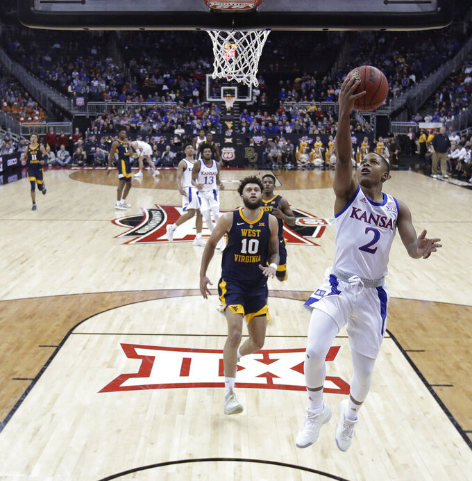 Kansas' Charlie Moore (2) gets past West Virginia's Jermaine Haley on the way to the basket during the second half of an NCAA college basketball game in the Big 12 men's tournament Friday, March 15, 2019, in Kansas City, Mo. Kansas won 88-74. (AP Photo/Charlie Riedel)