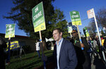 Rep. Eric Swalwell, D-Calif., center, marches with Oakland Education Association President Keith Brown, center right, along with teachers and supporters outside of Manzanita Community School in Oakland, Calif., Thursday, Feb. 21, 2019. Teachers in Oakland, California, went on strike Thursday in the country's latest walkout by educators over classroom conditions and pay. (AP Photo/Jeff Chiu)