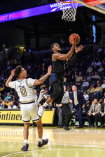 Pittsburgh guard Xavier Johnson (1) makes a layup past Georgia Tech guard Michael Devoe (0) during the first half of an NCAA college basketball game Wednesday, Feb. 20, 2019, in Atlanta. (AP Photo/Danny Karnik)