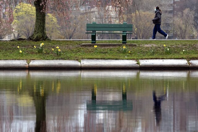 A woman wearing a protective mask walks along the Esplanade, Friday, May 1, 2020, in Boston. (AP Photo/Michael Dwyer)