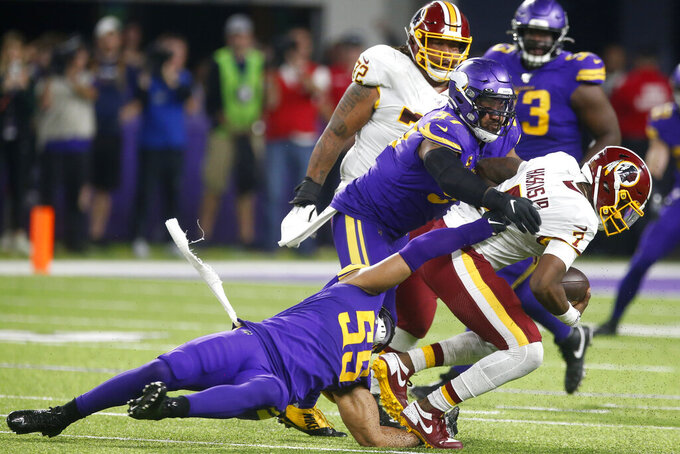 Washington Redskins quarterback Dwayne Haskins (7) is sacked by Minnesota Vikings defenders Anthony Barr (55) and Everson Griffen (97) during the second half of an NFL football game, Thursday, Oct. 24, 2019, in Minneapolis. (AP Photo/Jim Mone)