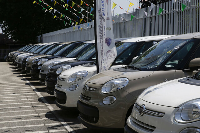 FILE  - In this Wednesday, July 25, 2018 file photo, cars are parked at a Fiat Chrysler car dealer in Milan, Italy. European car sales bottomed out last month as the automotive industry faces the worst crisis in decades.   Strict lockdown measures to contain the coronavirus shutdown most dealerships across the continent for the full month of April, amid a precipitous drop in consumer spending, causing sales to collapse by an unprecedented 76%, according to the ACEA car manufacturers' association. (AP Photo/Luca Bruno, File)