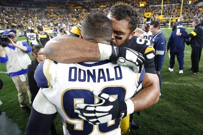Pittsburgh Steelers defensive end Cameron Heyward (97) and Los Angeles Rams defensive tackle Aaron Donald (99) hug on the field following an NFL football game in Pittsburgh, Sunday, Nov. 10, 2019. The Steelers won 17-12. (AP Photo/Don Wright)