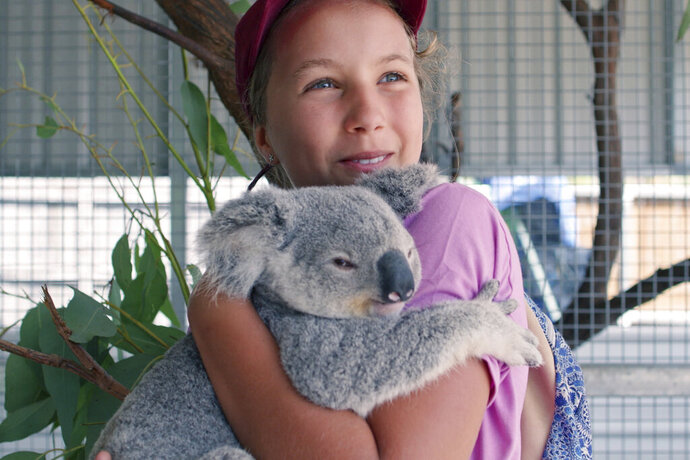 This image released by Netflix shows Izzy Bee holding a koala bear in a scene from
