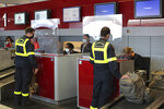 Members of the Securite Civile rescue organisation wait at the boarding desk at Charles de Gaulle airport, north of Paris, Wednesday, Aug.5, 2020. France is sending two planes to Lebanon on Wednesday with dozens of emergency workers, a mobile medical unit and 15 tons of aid. The aid is expected to arrive Wednesday afternoon and should allow for the treatment of some 500 blast victims, according to French President Emmanuel Macron's office. (AP Photo/Thibault Camus)
