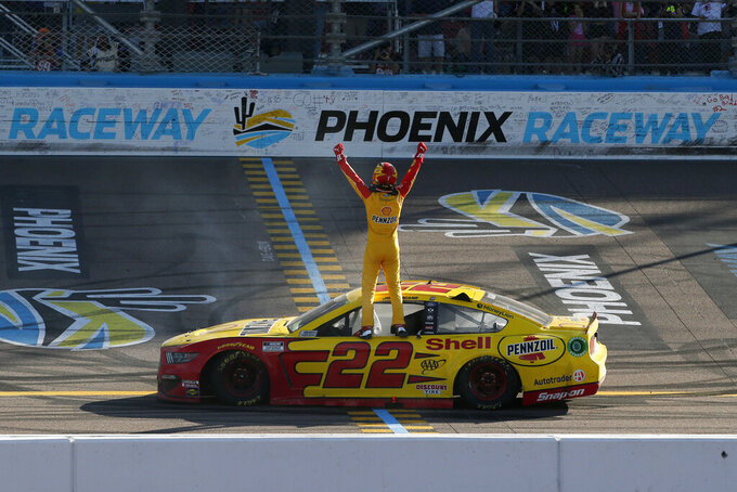 Driver Joey Logano stands on his race car at the start-finish line as he celebrates after winning the NASCAR Cup Series auto race at Phoenix Raceway, Sunday, March 8, 2020, in Avondale, Ariz. (AP Photo/Ralph Freso)