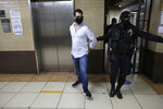 The son of former Panamanian President Ricardo Martinelli, Ricardo Martnelli Linares, is lead by an officer before a hearing at the judicial court building in Guatemala City, Monday, July 6, 2020. Guatemalan police detained Ricardo Martnelli Linares and his brother Luis Enrique Martnelli Linares on an Interpol warrant for money laundering, as they attempted to board a private plane out of the country. (AP Photo/Moises Castillo)