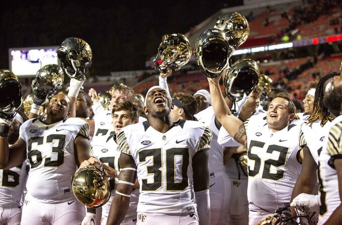 Wake Forest's Ja'Cquez Williams (30) celebrates with his team after defeating North Carolina State in an NCAA college football game in Raleigh, N.C., Thursday, Nov. 8, 2018. (AP Photo/Ben McKeown)