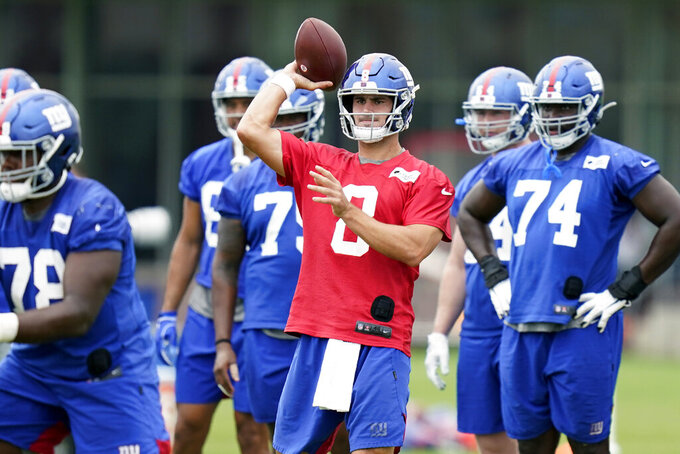 FILE - In this Wednesday, Aug. 19, 2020 file photo, New York Giants quarterback Daniel Jones, center, participates in a practice at the NFL football team's training camp in East Rutherford, N.J. Daniel Jones is heading into his second season with the New York Giants in a different position. The skinny kid from Duke is no longer the heir apparent at quarterback to two-time Super Bowl MVP Eli Manning, who retired after last season.(AP Photo/Seth Wenig, File)