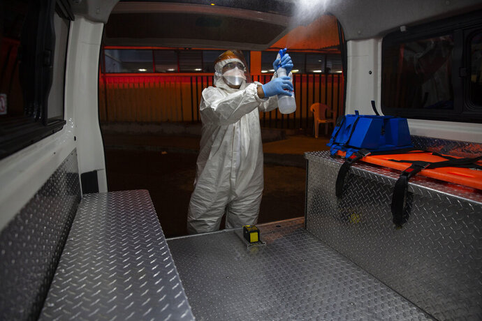A firefighter wearing gear to protect against the coronavirus disinfects an ambulance outside the COVID-19 unit at San Juan de Dios hospital in Guatemala City, Monday, June 8, 2020. (AP Photo/Moises Castillo)