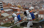 FILE - In this April 28, 2020, file photo, city workers disinfect a stairway in attempt to help contain the spread of the new coronavirus, in La Paz, Bolivia. Even amid a global pandemic, there's no sign that corruption is slowing down in Latin America. Perhaps the biggest case is in Bolivia, where the health minister was arrested amid allegations that officials bought 170 ventilators at inflated prices. (AP Photo/Juan Karita, File)