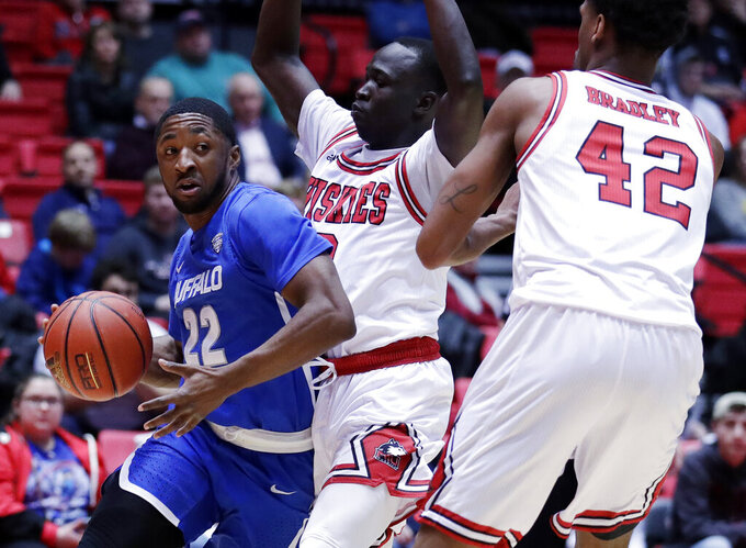 Buffalo guard Dontay Caruthers, left, looks to pass against Northern Illinois guard Gairges Daow, center, and Levi Bradley during the first half of an NCAA college basketball game Tuesday, Jan. 22, 2019, in DeKalb, Ill. (AP Photo/Nam Y. Huh)