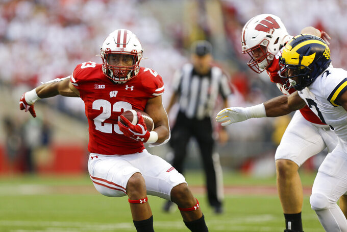 Wisconsin running back Jonathan Taylor runs against Michigan linebacker Khaleke Hudson during the first half of an NCAA college football game Saturday, Sept. 21, 2019, in Madison, Wis. (AP Photo/Andy Manis)