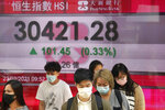 People wearing face masks walk past a bank's electronic board showing the Hong Kong share index in Hong Kong, Tuesday, Feb. 23, 2021. Asian shares were mostly higher on Tuesday despite a sell-off in technology companies on Wall Street.(AP Photo/Kin Cheung)